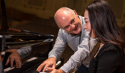 Simon Rowe with student at a grand piano